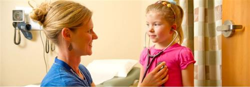 Nurse practitioner Carrie Kingsley lets a young girl listen to her heartbeat with a stethoscope.